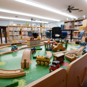 Kids play table at the library, with wooden trains on it.